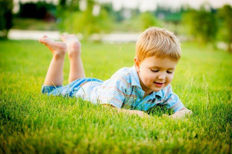 kid laying on grass